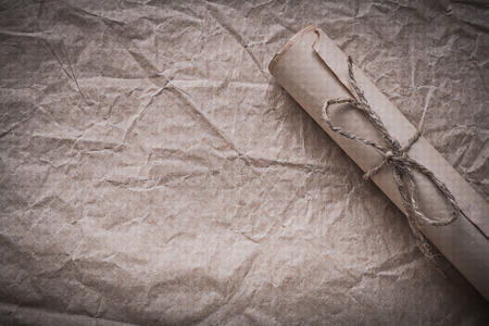 rolled paper: Vintage rolled paper on crumpled wrapping sheet. Stock Photo