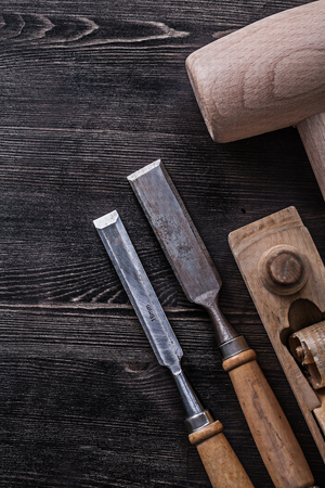 chisels: Flat chisels wooden hammer planer on wood board construction concept. Stock Photo