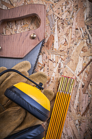 leather gloves: Protective leather gloves wooden meter handsaw earmuffs on OSB. Stock Photo