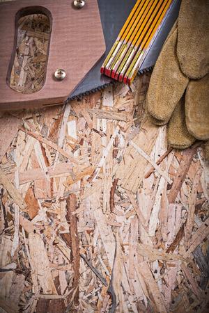 serrucho: guantes de cuero de seguridad serrucho madera de un metro sobre tablero aglomerado.