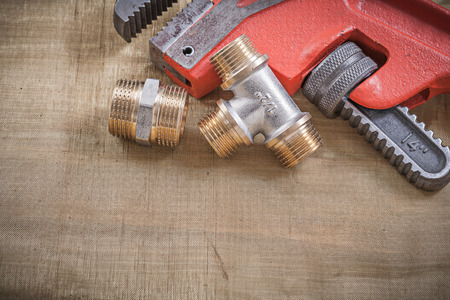 household fixture: Monkey wrench pipe fittings on mesh filter grid. Stock Photo