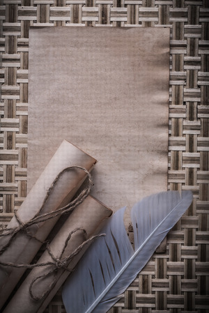 pack string: Medieval blank sheet rolled paper feather on wicker wooden mat.