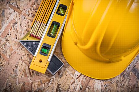 osb: Square ruler construction level hard hat wooden meter on OSB.