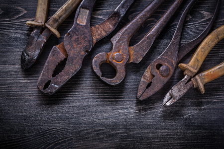 snips: Rusty nippers pliers tin snips wire-cutter on wooden board.