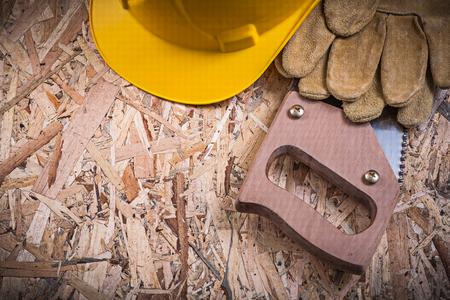serrucho: guantes de cuero de seguridad en edificios sierra de mano casco en madera aglomerada.