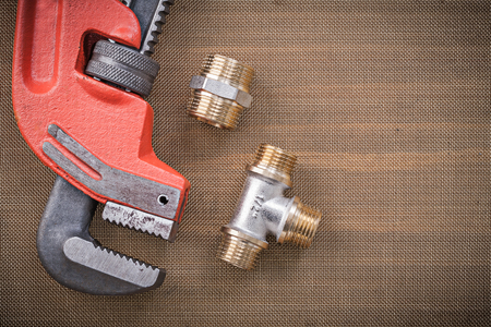 fixtures: Pipe wrench brass plumbing fixtures on cleaning mesh filter grid.