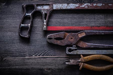 serrucho: Oxidados alicates serrucho vendimia alicates en el concepto de la construcci�n tarjeta de madera. Foto de archivo