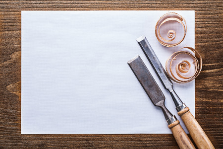 scobs: Clean sheet of paper wooden shavings flat chisels construction concept.