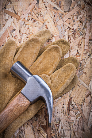 protective gloves: Claw hammer pair of leather protective gloves on OSB.