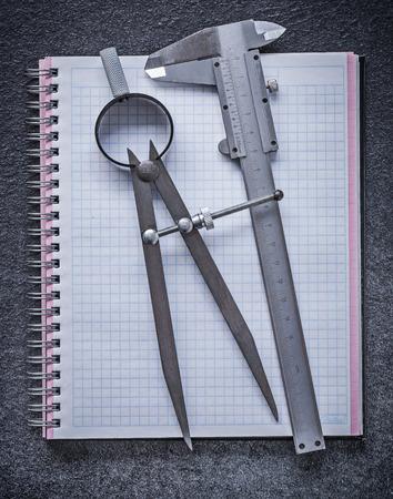 compas de dibujo: Compás de dibujo pie de rey cuaderno en el fondo negro concepto de la construcción.