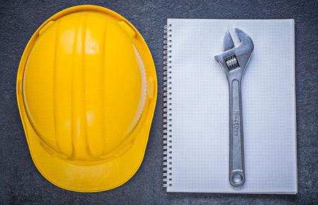 Notebook building helmet adjustable wrench on black background construction concept.