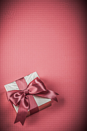 red ribbon bow: Gift box with tied ribbon on red background holidays concept.