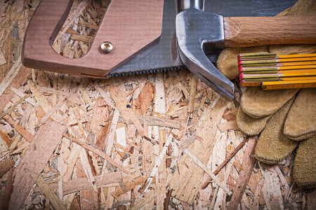 leather gloves: Protective leather gloves wooden meter hacksaw claw hammer on OSB.