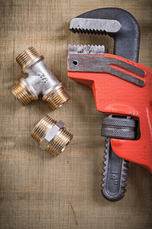 pipe wrench: Pipe wrench plumbing fixtures on mesh filter grid. Stock Photo