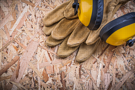 protectors: Safety leather gloves hard hat ear protectors on chipboard.