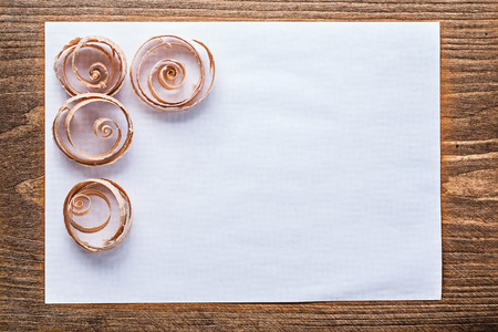 curled: Clean sheet of paper curled wooden shavings construction concept.