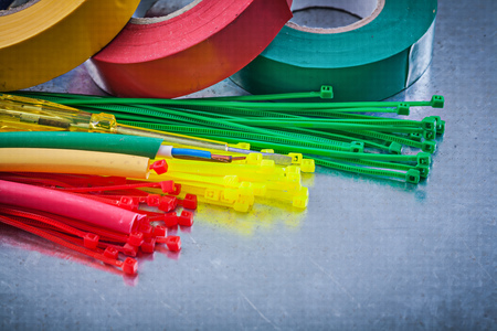 cable tie: Insulating tapes plastic cable ties electric wires on metallic background.