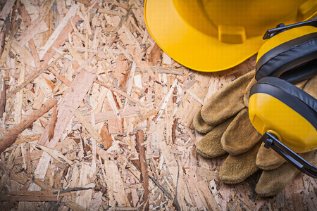 osb: Safety leather gloves hard hat ear muffs on OSB. Stock Photo