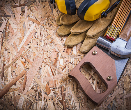 Earmuffs: Safety gloves wooden meter handsaw claw hammer earmuffs on OSB. Stock Photo