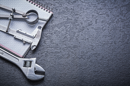 close up  wrench: Divider calliper adjustable spanner notebook construction concept.