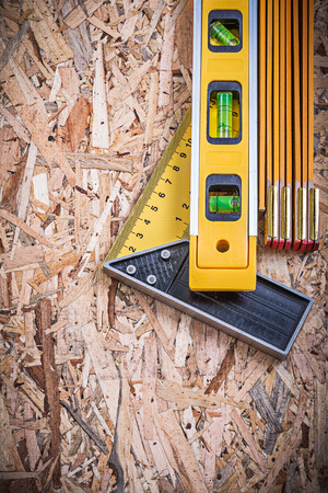 construction level: Square ruler construction level wooden meter on chipboard. Stock Photo