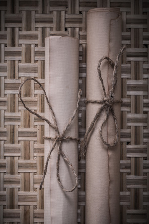 corded: Vintage corded scrolls of paper on wicker background.