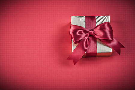 red glittery: Gift box on red background holidays concept.