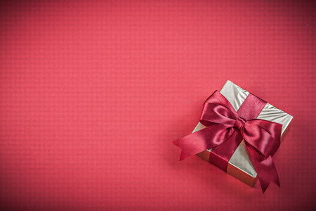 red glittery: Gift container with tied ribbon on red background holidays concept. Stock Photo