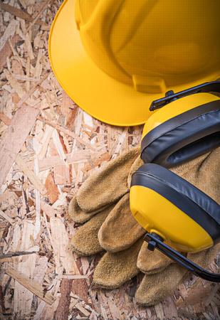 Earmuffs: Safety leather gloves hard hat earmuffs on OSB. Stock Photo