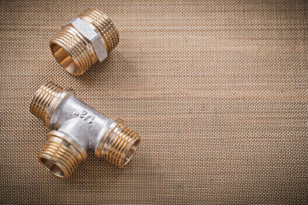 fittings: Brass plumber fixtures pipe fittings on water mesh filter. Stock Photo