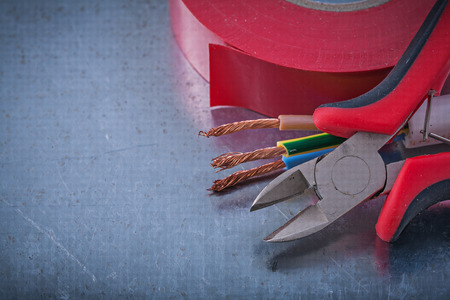 nippers: Insulation tape nippers electric wires on metallic background construction concept.