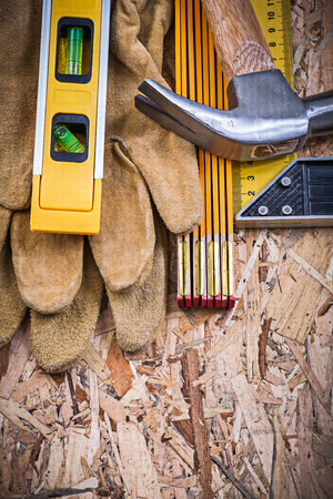 claw hammer: Claw hammer working gloves construction level wooden meter square ruler. Stock Photo