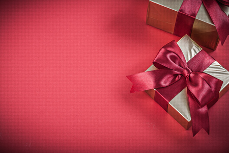 red glittery: Packed present containers with bow on red background holidays concept.