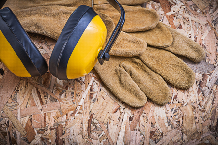 osb: Safety leather gloves ear muffs on OSB.