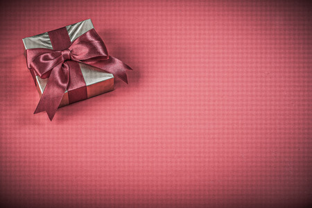 red glittery: Present container with tied bow on red background holidays concept.