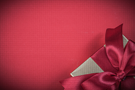 red glittery: Present box with tied bow on red background holidays concept.