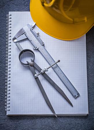 vernier caliper: Notebook building helmet drawing compass vernier caliper construction concept. Stock Photo