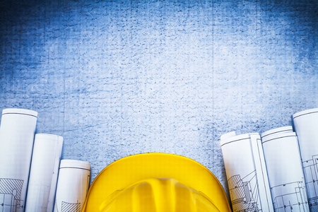 Copy space image of blueprints with protective hard hat on silver-metal vintage scratched surface construction concept.