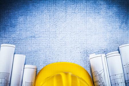 Kopieer ruimte afbeelding van blauwdrukken met beschermende helm op zilver metaal vintage gekrast oppervlak bouwconcept.