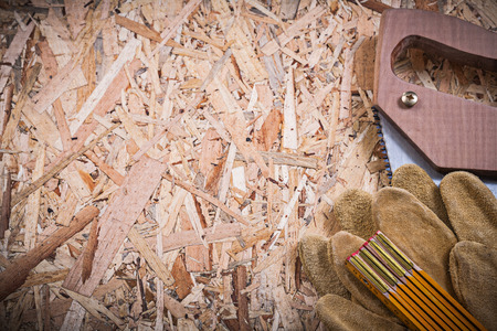 osb: Protective leather gloves wooden meter handsaw on OSB.