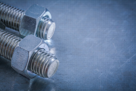threaded: Threaded bolt details and screw-nuts on metallic surface construction concept.