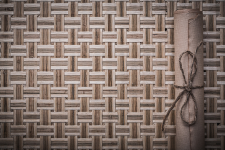 corded: Vintage medieval rolled corded paper on woven wooden matting.