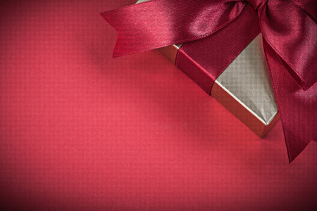 red glittery: Wrapped gift box on red background holidays concept.