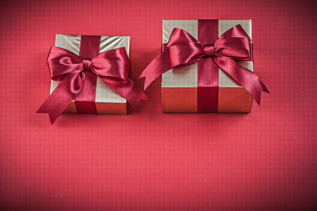 wrapped gift: Wrapped gift container with bow on red background holidays concept.