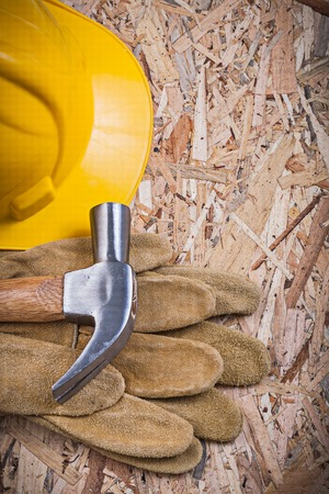 osb: Claw hammer hard hat protective gloves on OSB construction concept.