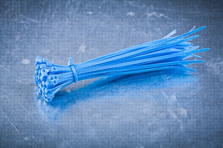 Blue plastic self-locking cable ties on metallic background construction concept. Stock Photo