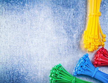 zip tie: Assortment of multicolored plastic cable ties on scratched metallic background.