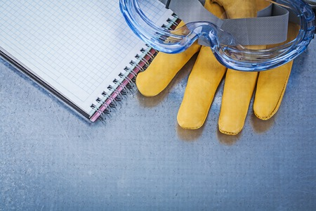 protective glasses: Set of protective glasses leather gloves copybook on metallic background. Stock Photo