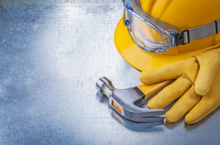 protective spectacles: Protective glasses gloves building helmet claw hammer on metallic background.