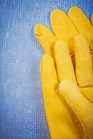 protective gloves: Leather protective gloves on metallic background electricity concept. Stock Photo
